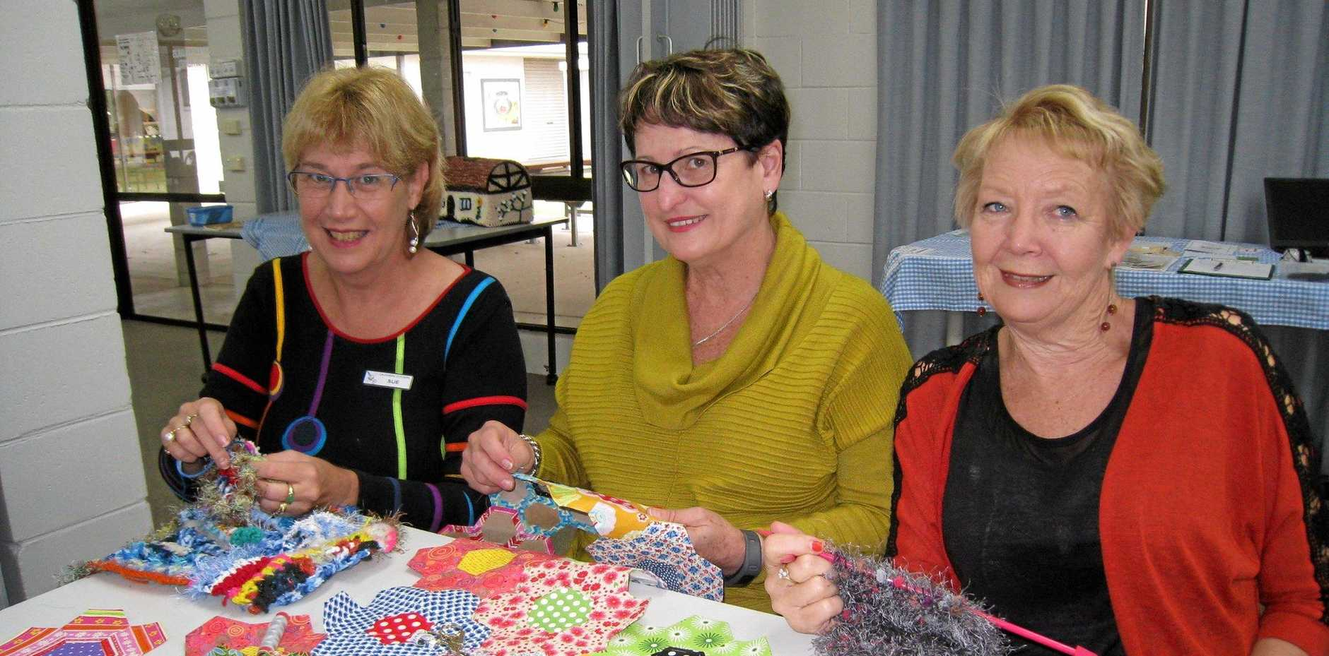 FAST FINGERS: Caloundra Arts Centre Association members Sue, Enrica and Kerrie prepare items for sale at the June Fair.