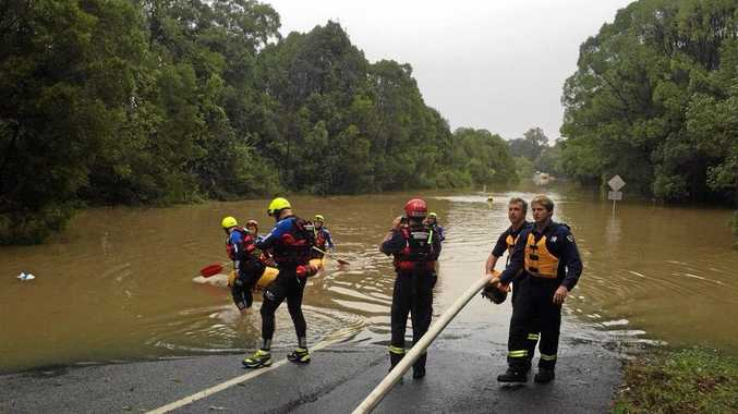 HELP AT HAND: A man is rescued by Rural Fire Service volunteers from floodwaters near Nana Glen, west of Coffs Harbour.