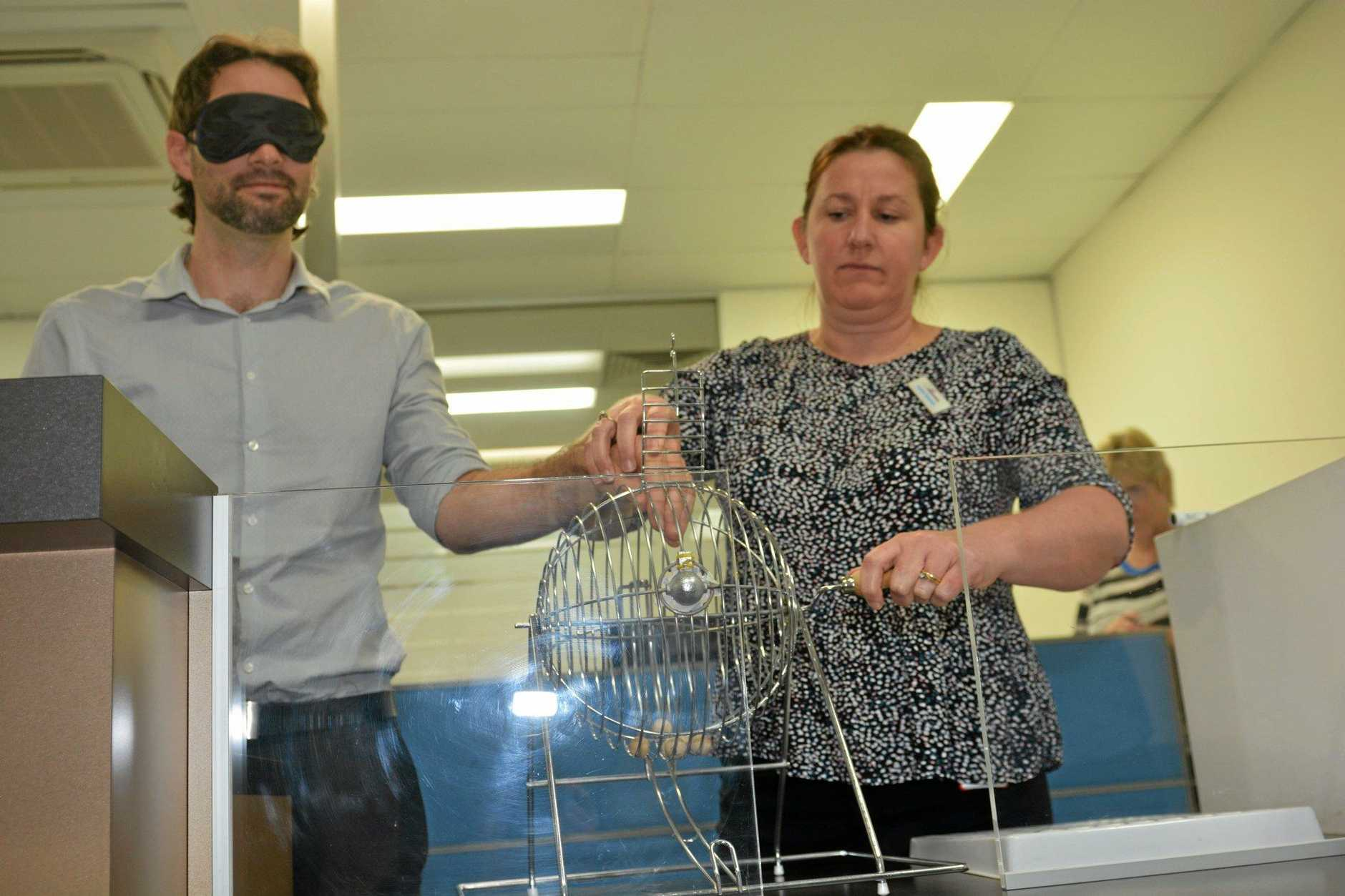 Australian Electoral Commission staff Brendan King and Jo Bowman conduct the blind draw for the 2016 Federal election ballot