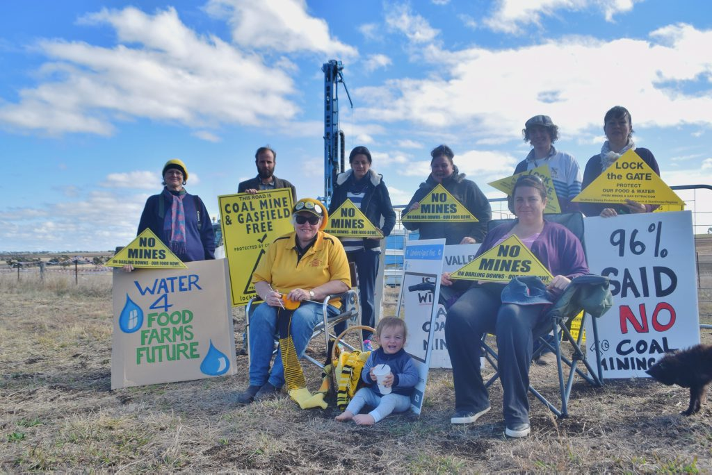 Southern Downs Protection Group members and residents Sarah Moles, Duncan Burnet, Marianne Irvine, Mandy Mutch, Taryn Turl, Fiona Gray, Lachlan Trimingham and Michelle Amos protest in front of the coal drilling rig at Mt Marshall.