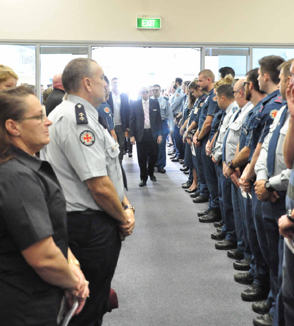 TRIBUTES FLOW: The Queensland Ambulance Service colleagues of Jim O'Donnell form a guard of honour at his funeral, where he was remembered as a loving family man and dedicated paramedic.