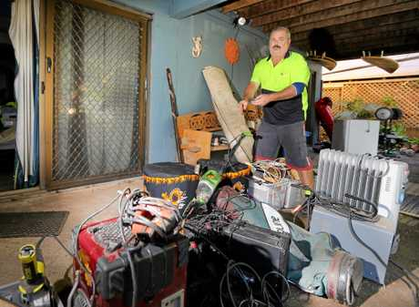 Warren Saxby throws out some of his water damaged belongings after the recent deluge and flooding.