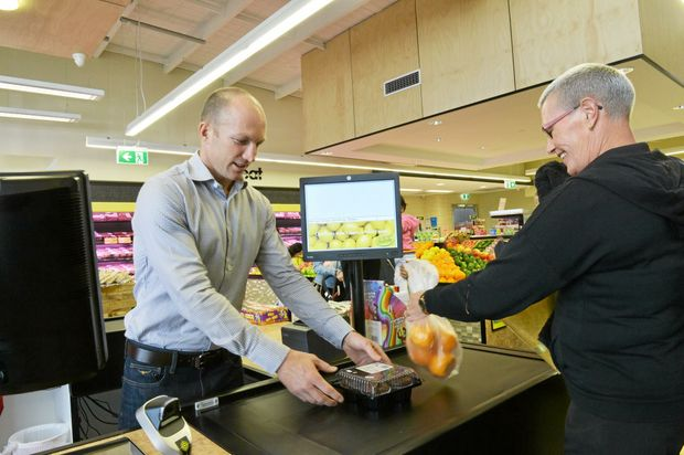 NATURAL: Darren Lockyer serving Pennie Andrews at the opening of the new Augustine Heights IGA.