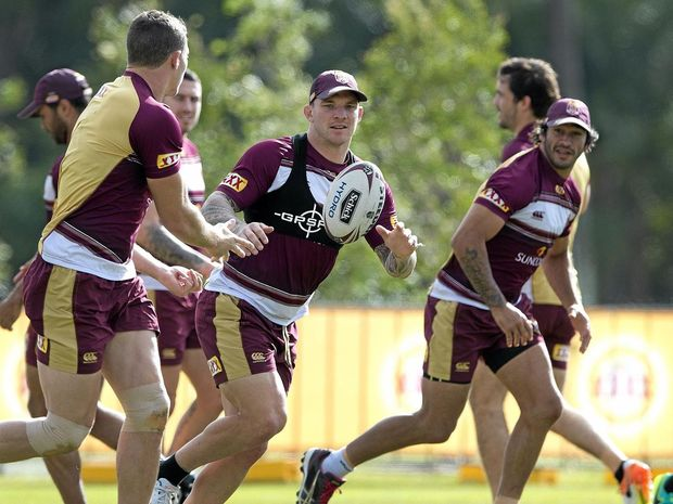 RIPPING IN: Josh McGuire (centre) receives the ball during the Queensland State of Origin team training session on the Gold Coast.