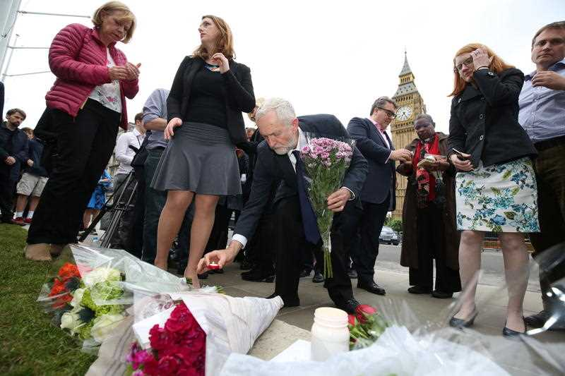 Labour Party leader Jeremy Corbyn, centre, lays a candle as he and deputy leader Tom Watson, centre rear, Thursday June 16, 2016, attend an impromptu vigil at Parliament Square opposite the Palace of Westminster, central London, following the death of Labour Member of Parliament, Jo Cox.