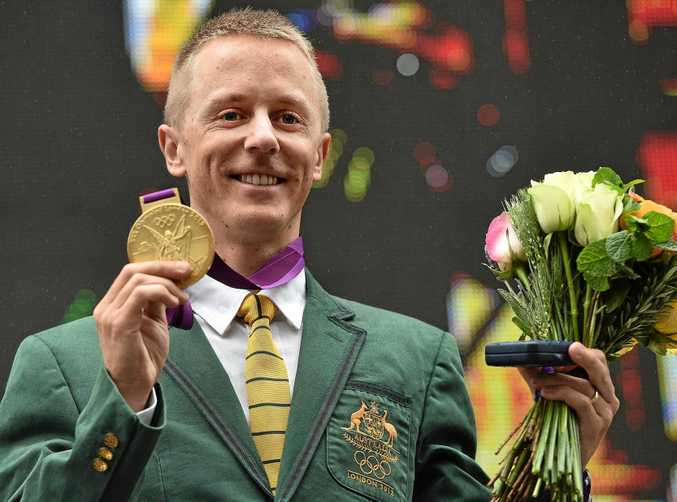 Australian athlete Jared Tallent is belatedly presented with the gold medal for the 50km walk at the 2012 London Olympics on the steps of the Treasury in Melbourne, Friday, June 17, 2016. The 50km walker will finally have his 2012 Olympic silver medal replaced by gold at a ceremony at the Treasury building in Melbourne at midday, after Russian Sergey Kirdyapkin was revealed as a drug cheat earlier this year and stripped of his title. (AAP Image/Julian Smith) NO ARCHIVING
