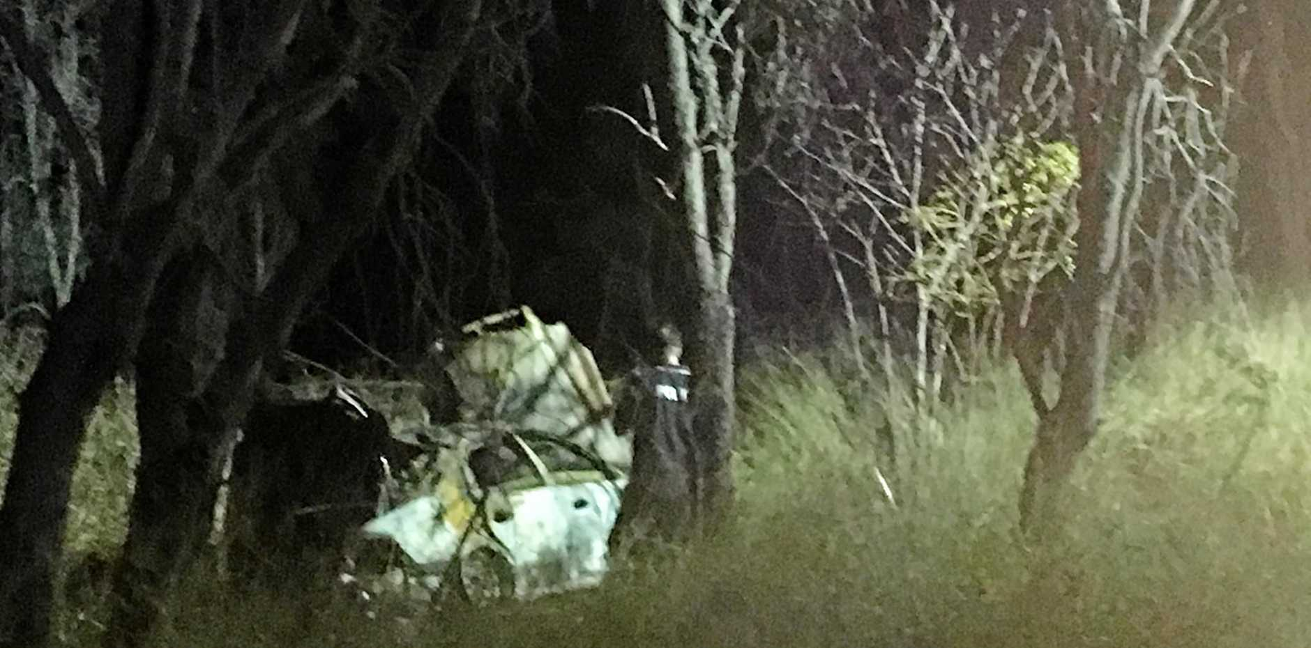 FATAL CRASH: Police inspect the burnt out vehicle in the Lockyer Valley on Saturday.