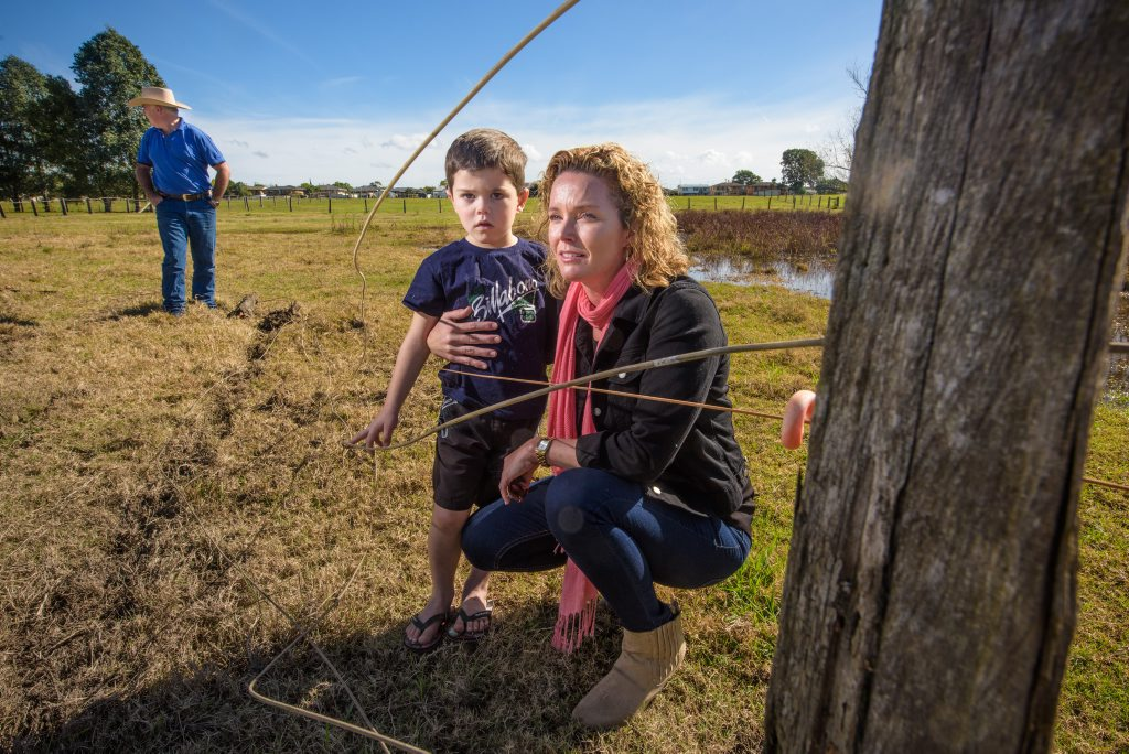 Beck Plunkett-Hicks and son Cooper with Steve Bell (rear) - look over the damage to fence and property an out of control car caused at the unsealed section of Prince Street.