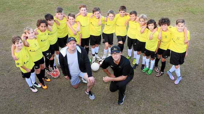 NR Football coaches Brett MacCracken and John Quinton surrounded by some of the academy's young players.