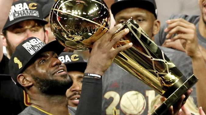 CROWNING GLORY: Cleveland Cavaliers star LeBron James holds up the Larry O'Brien Trophy after beating the Golden State Warriors in the NBA finals game seven at Oracle Arena in Oakland.