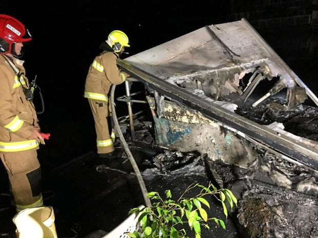 Tweed Heads firefighters douse a fire that destroyed a houseboat at West Tweed.