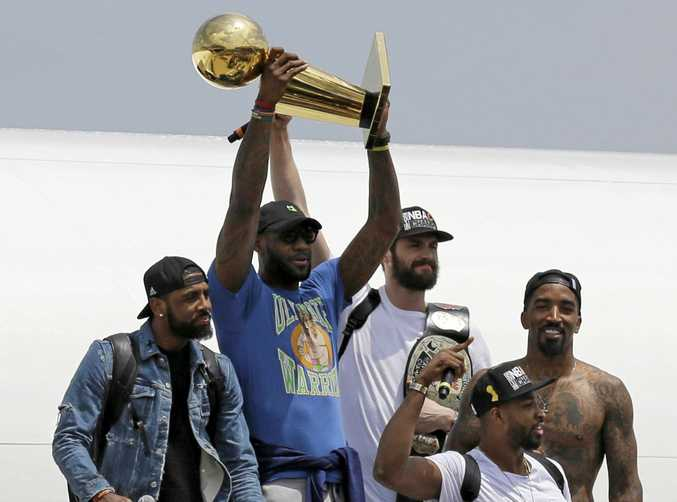TRIUMPHANT HOMECOMING: Cavaliers star LeBron James holds up the Larry O'Brien Trophy with the team in Cleveland.