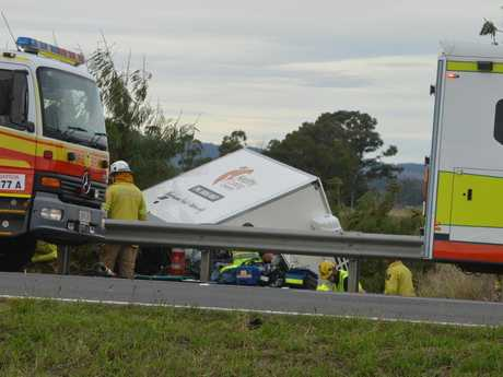 Emergency crews are working to free a man trapped inside a small truck which rolled over on the Warrego Highway at Gatton.