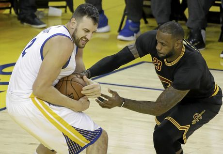 Cleveland Cavaliers forward LeBron James (right) reaches for the ball as he defends Golden State Warriors centre Andrew Bogut.