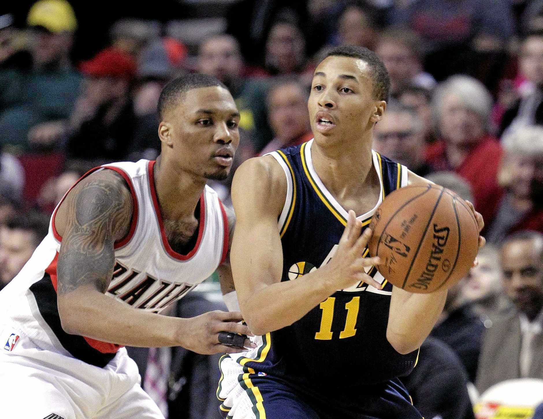 Utah Jazz guard Dante Exum, from Australia, right, works the ball against Portland Trail Blazers guard Damian Lillard during the first half of an NBA basketball game in Portland, Ore., Tuesday, Feb. 3, 2015.  (AP Photo/Don Ryan)