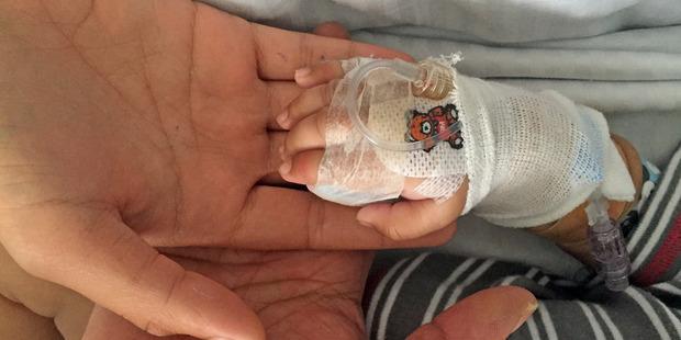 Baby Hamish is battling meningococcal meningitis in Tauranga Hospital. Mum Ashley holds his hand, with grandmother Charmaigne.