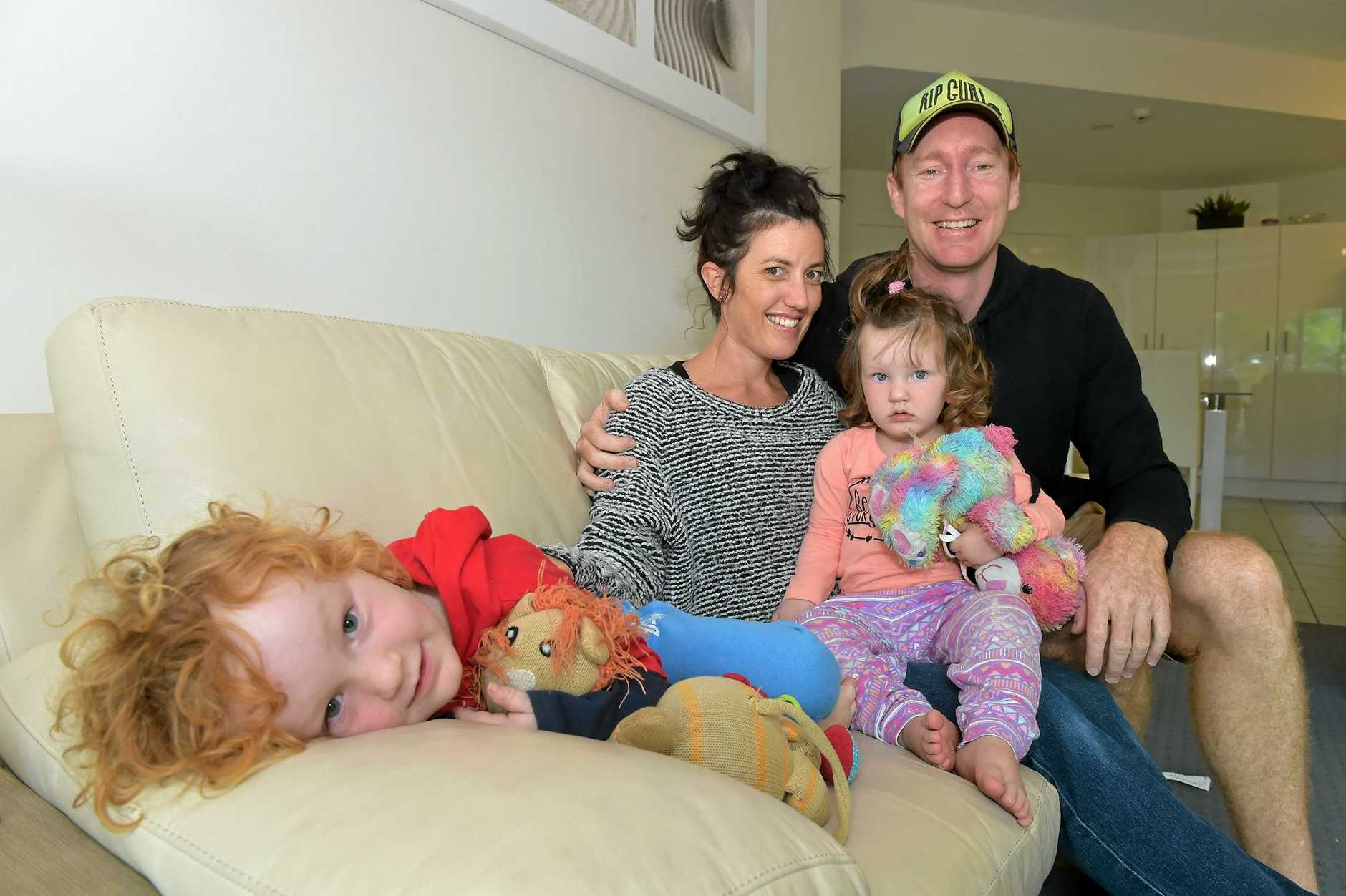 Akeringa Place residents Carl and Tracey Hunt with their children Archie and Evie are staying at a unit in Mooloolaba after the roof of their home was blown off in a storm.
