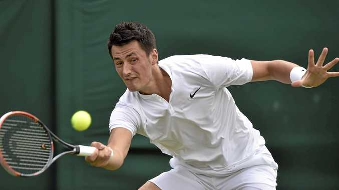 THROUGH AT LAST: Bernard Tomic of Australia returns to Fernando Verdasco of Spain during their first-round match of the Wimbledon Championships at the All England Lawn Tennis Club in London.