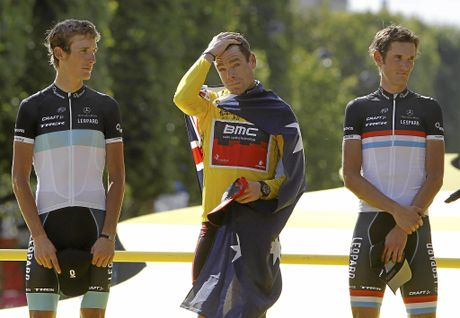Cadel Evans of Australia, wearing the overall leader's yellow jersey, reacts to the singing of the Australian national anthem as he stands on the podium after winning the Tour de France in 2011.