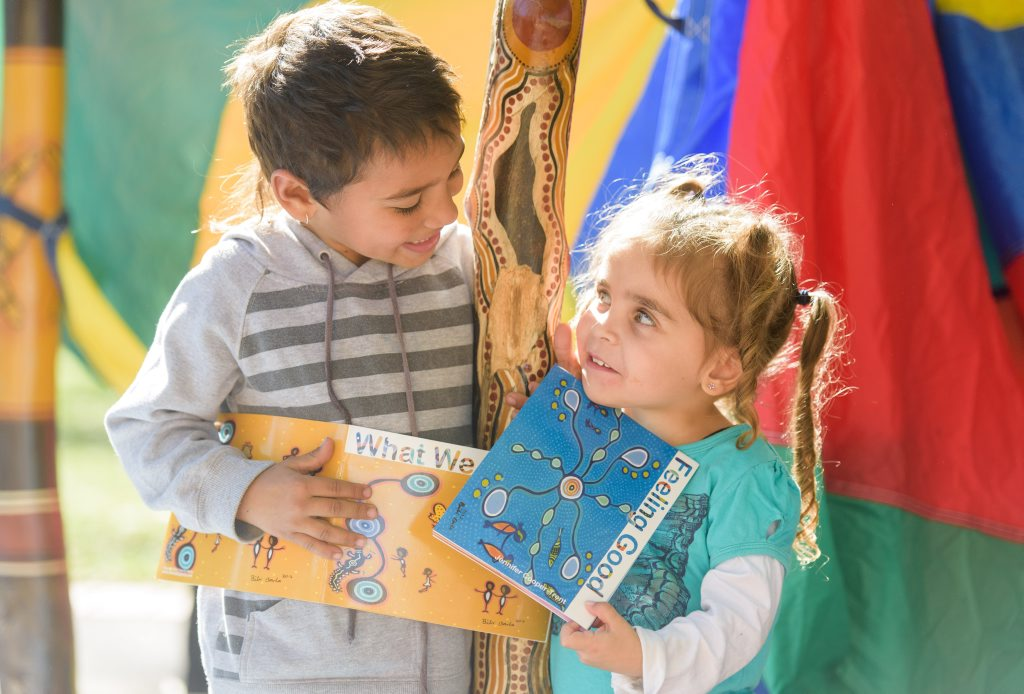Khyrin Martin-Walker and Annalyse Dwyer get into some reading around the totems at the Gummyaney Aboriginal Preschool NAIDOC day.