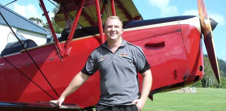HERO: Pilot Nick Rorison standing with a Tiger Moth Adventures plane. Photo contributed.