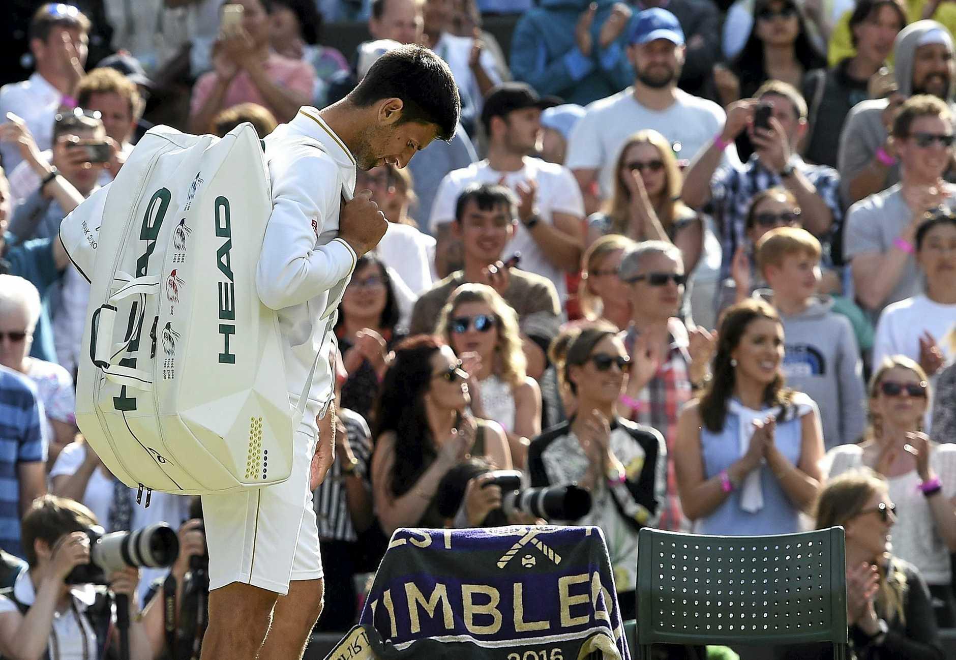 Novak Djokovic walks off court following his defeat by Sam Querrey.