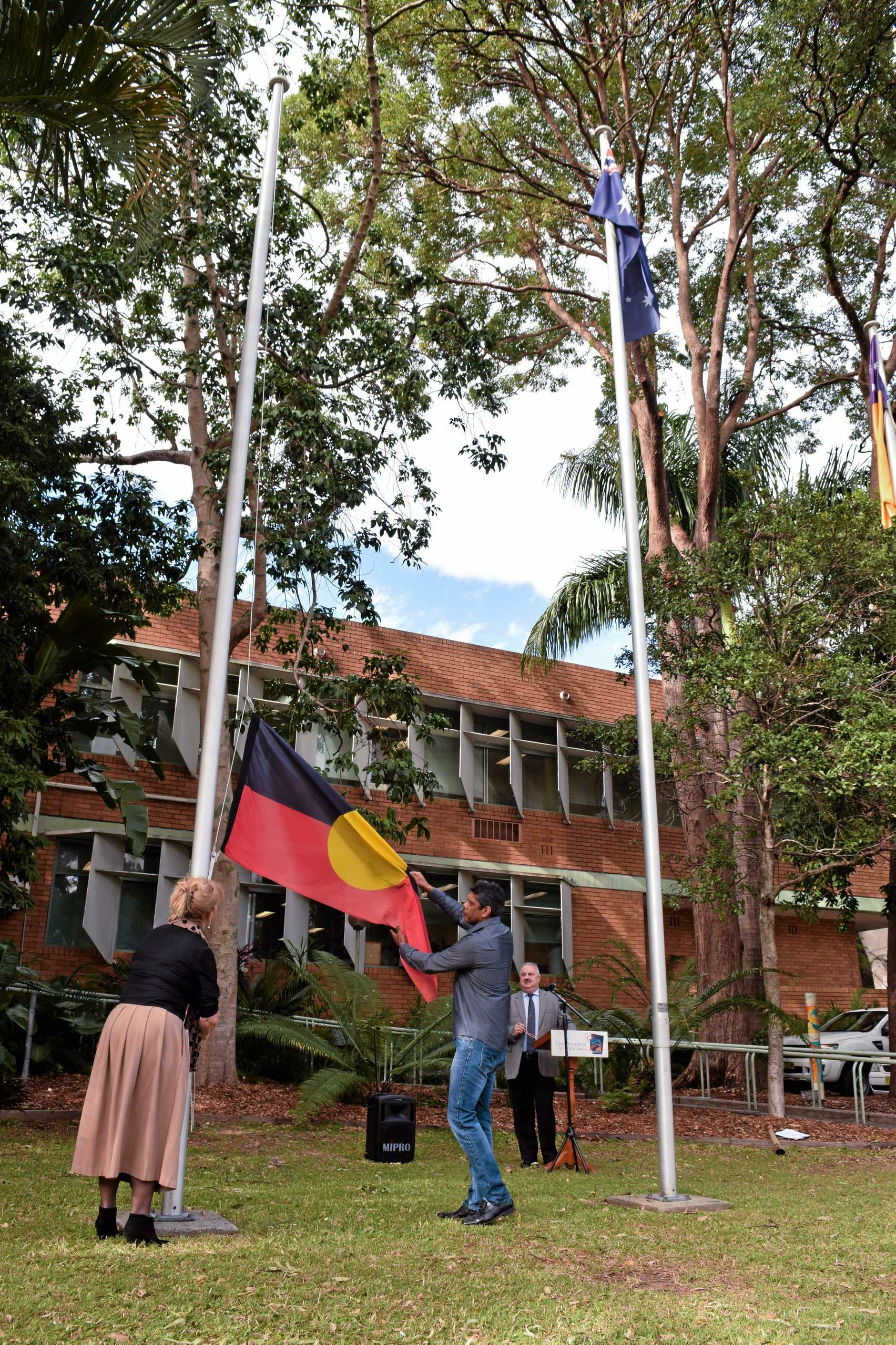 Mayor Denise Knight raising the Aboriginal flag with CHASE treasurer Lloyd Lynwood at the official opening of NAIDOC Week 2016 in Coffs Harbour.