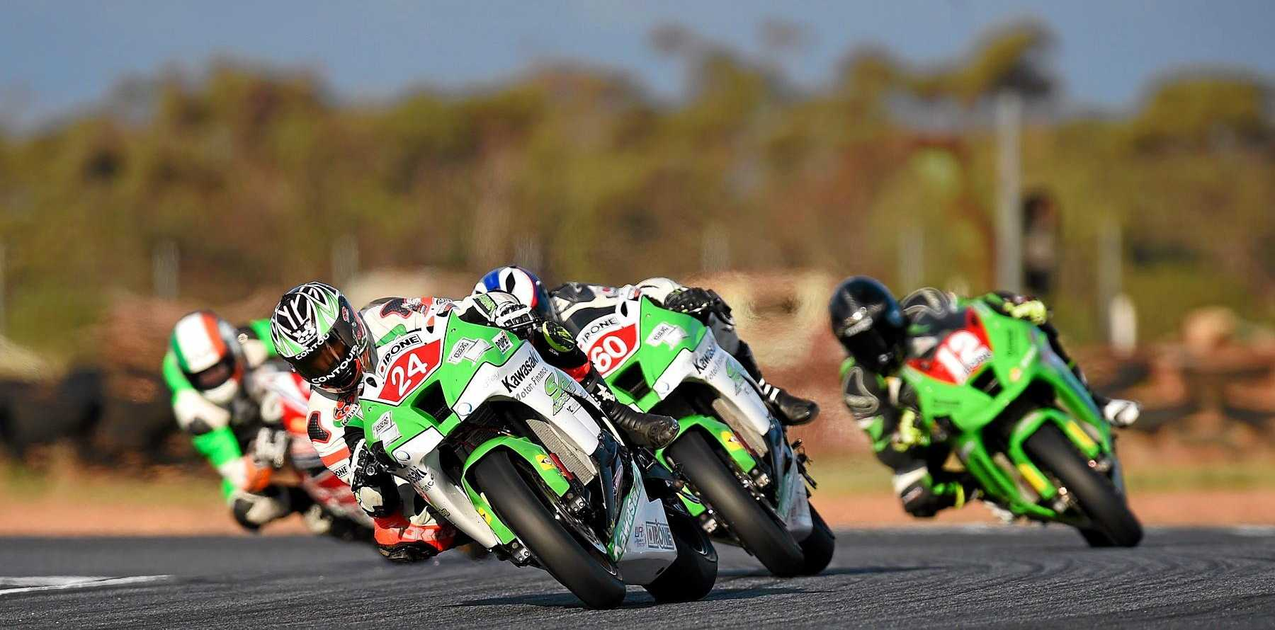 Superbike rider Robbie Bugden (number 24) leads the field in an Australasian Superbike Championship race.
