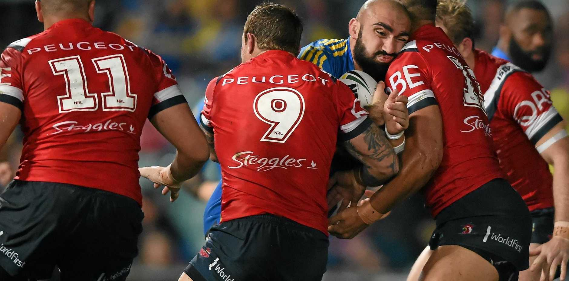 TOUGH STUFF: Tim Mannah of the Eels is tackled by Jake Friend and Isaac Liu of the Roosters.