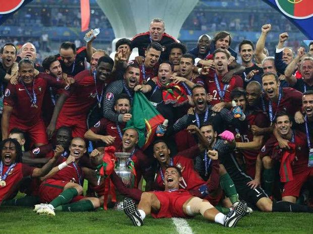 Portugal's Cristiano Ronaldo, bottom, celebrates with team mates winning the Euro 2016 final soccer match between Portugal and France at the Stade de France in Saint-Denis, north of Paris, Sunday, July 10, 2016.