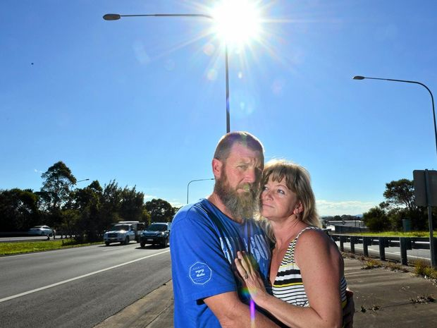 LUCKY ESCAPE: Tracey Sampson with her husband Scott at the scene where she ran over a fallen light pole on the Sunshine Motorway.