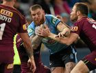 TOUGH STUFF: Josh Dugan of the Blues is tackled by Gavin Cooper of the Maroons.