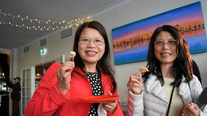A TASTE OF THE REGION: Taiwanese delegates Lisa Ou and May Hsiao enjoy Fraser Island prawns.
