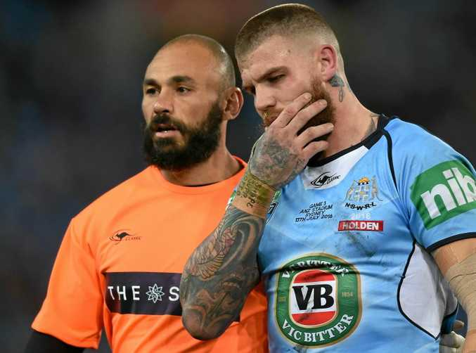 INJURY CURSE: Josh Dugan of the Blues holds his jaw as he is helped from the field by a trainer during State of Origin game three.