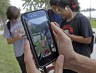 "Pinsir, a Pokemon, is found by a group of Pokemon Go players, Tuesday, July 12, 2016, at Bayfront Park in downtown Miami. The ""Pokemon Go"" craze has sent legions of players hiking around cities and battling with ""pocket monsters"" on their smartphones. (AP Photo/Alan Diaz)"