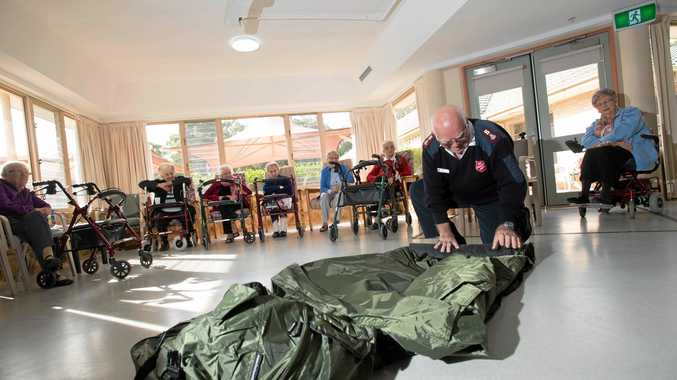 DONATION: Coffs Harbour Salvation Army major Russell Grice demonstrates how the donated camp beds from Mater Christi will be used.