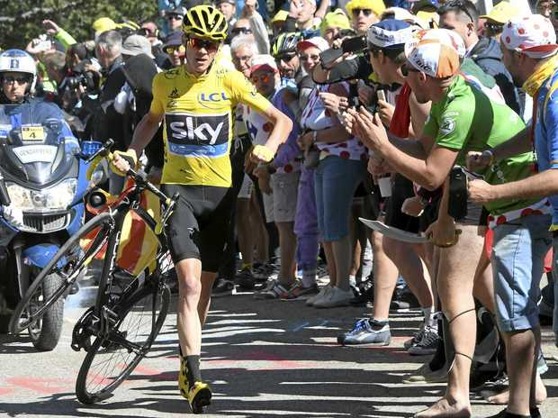BIZARRE FINALE: Britain's Chris Froome, wearing the overall leader's yellow jersey, runs with his bike after he crashed at the end of the 12th stage of the Tour de France.