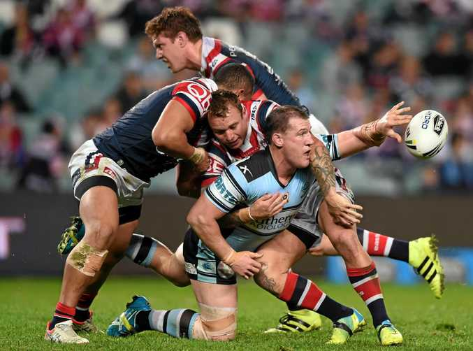 KEEPING IT ALIVE: Paul Gallen gets an offload away for the Sharks while being tackled by the Roosters defence during last night's round 19 NRL clash at Allianz Stadium in Sydney.