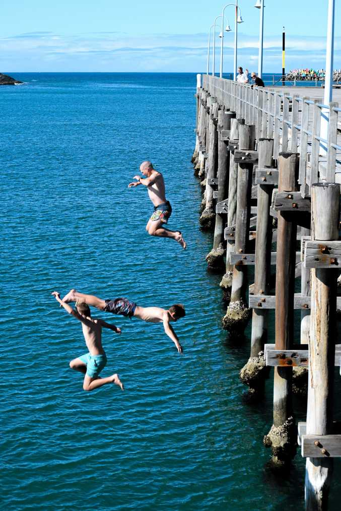 DIVING IN: Local Matt O'Garey jumping off the jetty with his son Harrison, 13 and a friend.