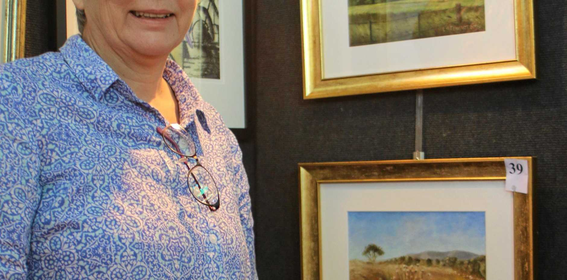 Artist and parish volunteer Linda Stewart with some of the landscapes she painted for the exhibition. Photo Sophie Lester / Warwick Daily News