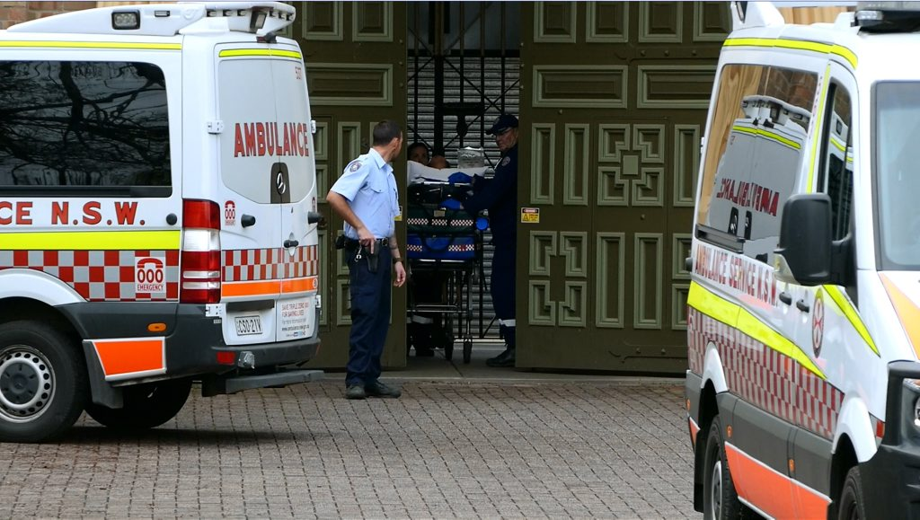 Ambulance officers transporting patients to hospital after a fire yesterday at Grafton Jail. photo: tim howard