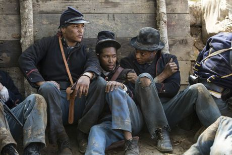 Rapper TI, left, and Reg -Jean Page, far right, in a scene from the TV series Roots.