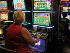 UNDER SCRUTINY: A woman tries her luck on a pokie machine.