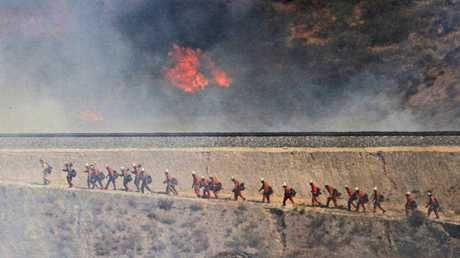 A fire crew approaches as a wildfire burns on Friday, July 22