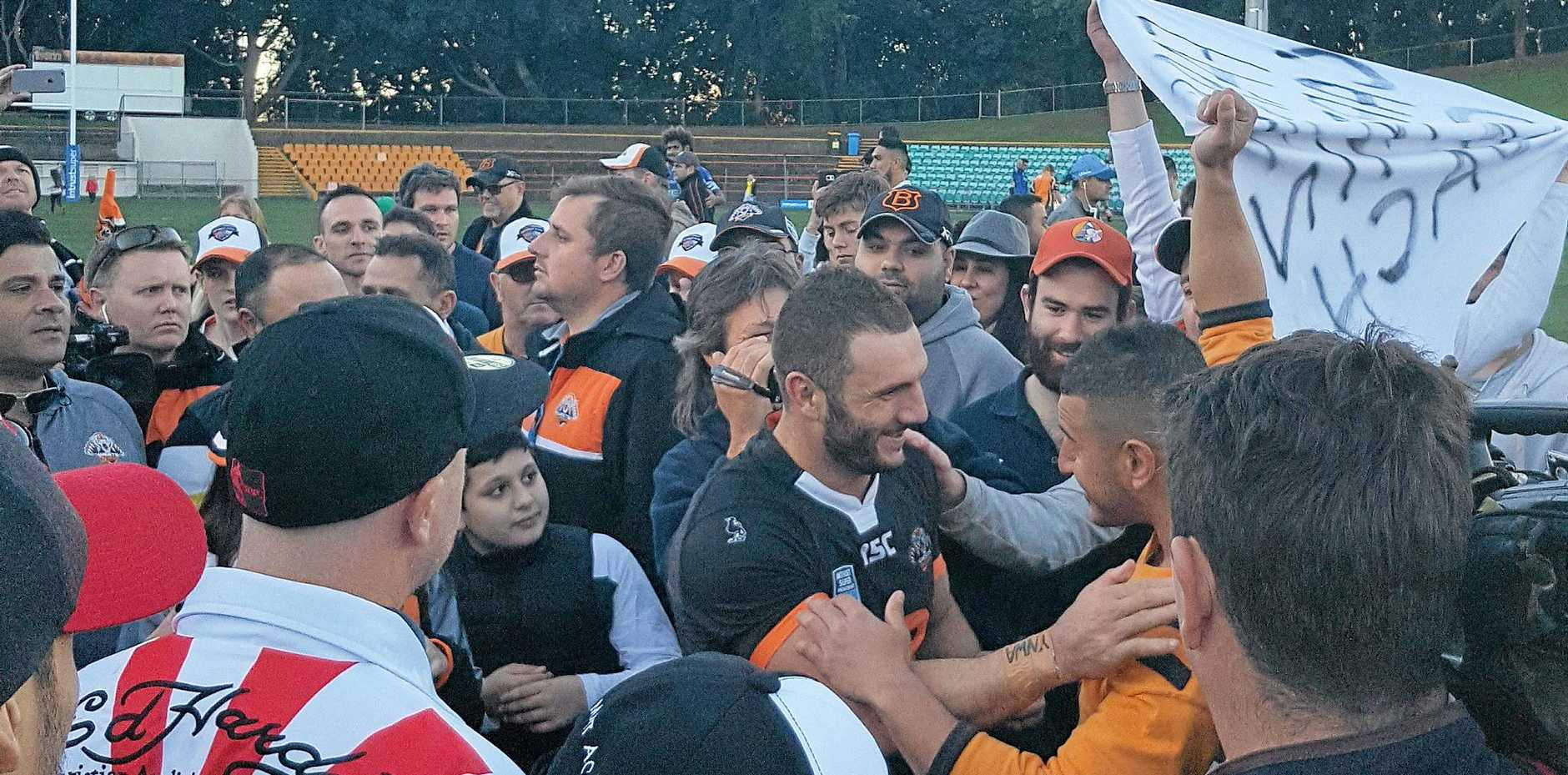 FAN FAVOURITE: Robbie Farah (centre) is swamped by fans after playing for Wests Tigers in their NSW Cup match against the Newtown Jets at Leichhardt Oval in Sydney.