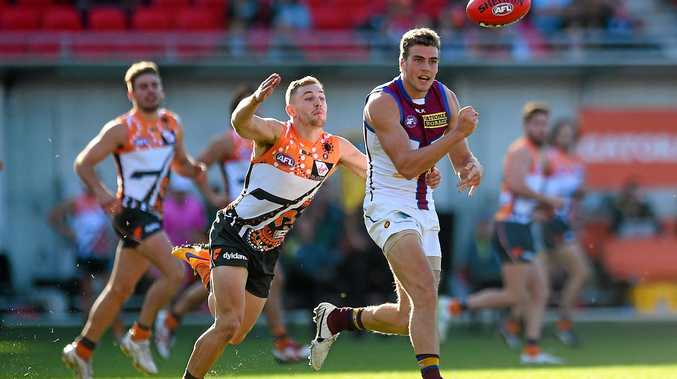 STAYING POSITIVE: Tom Cutler of the Lions hand passes in a game against the GWS Giants.