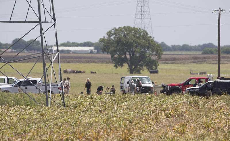 Investigators surround the scene in a field near Lockhart, Texas where a hot air balloon carrying at least 16 people collided with power lines Saturday, July 30, 2016, causing what authorities described as a