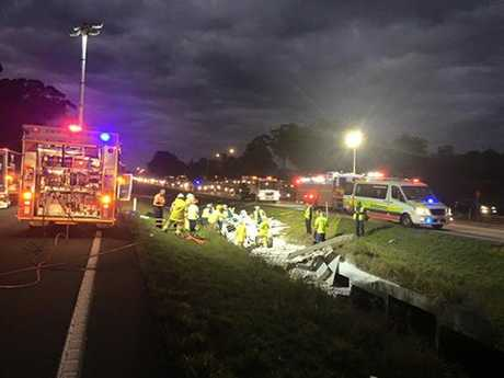 Emergency services are working to free two men trapped after a truck crash on the Bruce Hwy.