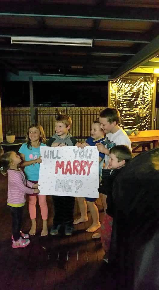 The kids hold the sign as Ellen walks outside.