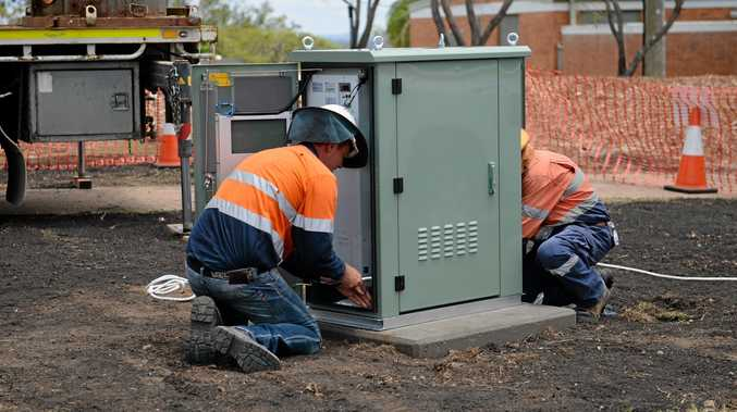 Workers install an NBN cabinet.